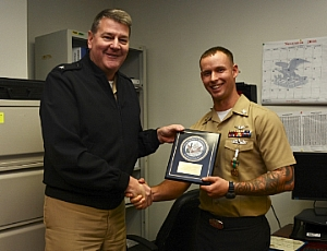 Rear Adm. Charles Rock, Commandant, Naval District Washington, presents Aviation Boatswain's Mate (Aircraft Handling) 1st Class (AW/SW) Timothy Godden with the a regional Junior Sailor of the Year plaque at the regional Junior Sailor of the Year (JSOY) presentation ceremony Dec. 20 at NAS Patuxent River. Godden, of Naval Air Station Patuxent River's Air Operations Department, was named the Naval District Washington JSOY for fiscal year 2016.
