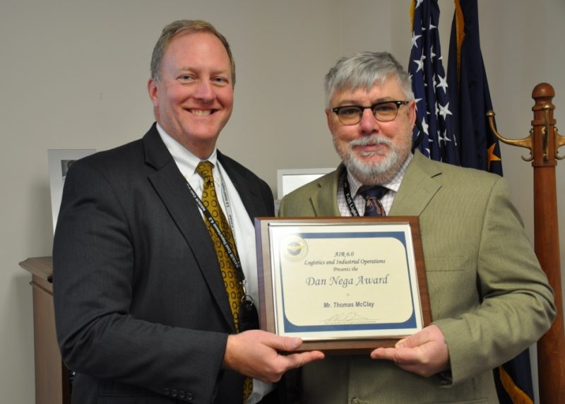 Thomas McClay, Naval Air Warfare Center Aircraft Division Total Asset Visibility (NAWCAD 6.8.3) competency manager (right), is congratulated by Daniel Nega, director of the Naval Air Systems Command (NAVAIR) Cost Estimating and Analysis Department, for being named the 2016 Daniel L. Nega Excellence in Logistics Leadership Award recipient at Naval Air Station Patuxent River, Maryland, Dec. 19. The award recognizes a Naval Air Systems Command (NAVAIR) Logistics and Industrial Operations (AIR-6.0) national civilian or military employee for excellence in commitment and dedication to the people, mission and professionalism of AIR-6.0. Nega, the award's namesake, commended McClay for his work to reduce component screening and marking cycle time at Fleet Readiness Centers, championing the career development of the NAWCAD 6.8.3 workforce, and for personally recruiting and mentoring five wounded warriors.