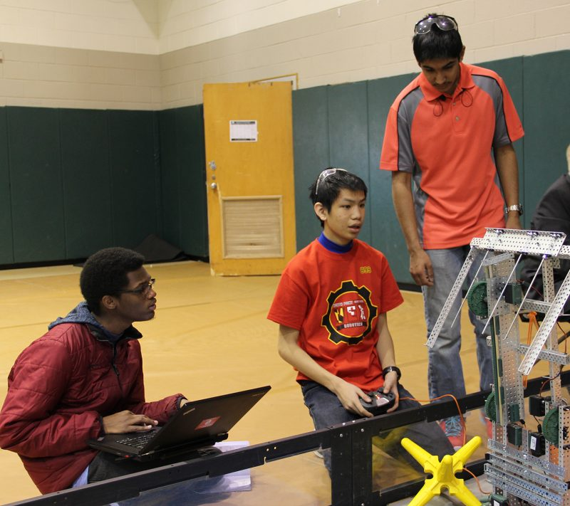 North Point High School students junior Jabari Grubb, left, sophomore Andrew Fan and junior Zaahid Ramakdawala confer about their robot during the Feb. 4 VEX Robotics competition at the College of Southern Maryland.