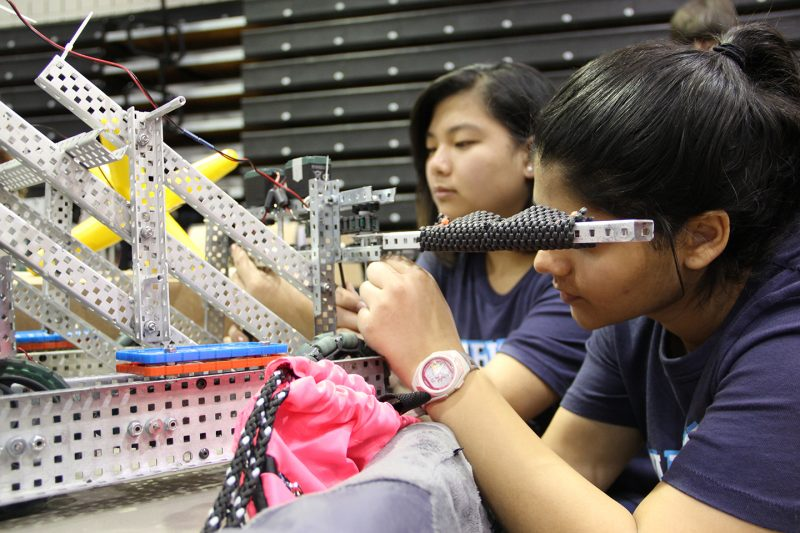 Members of La Plata High School's VEX Robotics team, Angle Warriors, sophomores Emily DePew, left, and Sophia Khan, work on their robot before the competition started Feb. 4 at the College of Southern Maryland.