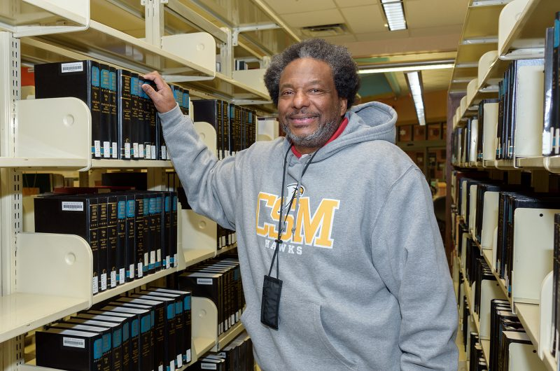 CSM student Benjamin Brown checks out the law books at a CSM library. Brown, a retiree, is working toward his associate degree at CSM with the ultimate goal of earning his law degree and becoming an attorney.