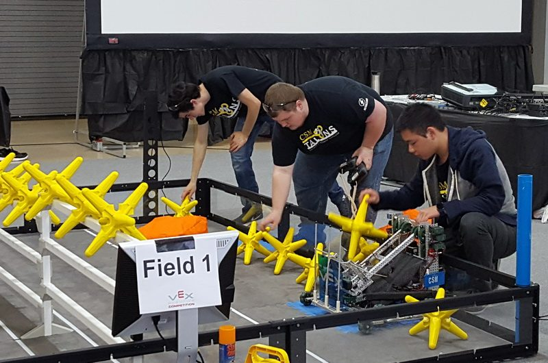 Members of the CSM Talons, from left, Ed Gesser of Mechanicsville, George Jenkins of La Plata and Wen Xing Lin of St. Leonard, with one of their robots in front, prepare their field before a match at Fairmont State University in Fairmont, West Virginia, March 10.