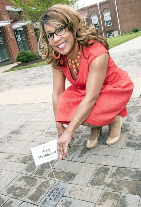 Mary Washington, longtime member of the St. Mary's County Board of Education, kneels beside the brick dedicated in her name at CSM's Leonardtown Campus.