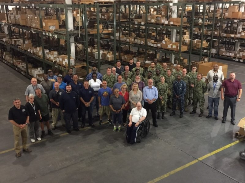 Some of the 105 Sailors, civilians and contractors who make up the NAVSUP Fleet Logistics Center Norfolk Det Patuxent River pose in the warehouse after receiving the Commander, Naval Air Forces™ Blue E Supply Excellence Award. The award, based on a combination of monthly effectiveness reports and a multiple-day Supply Management Inspection (SMI), is given after careful evaluation of supply and materiel management, including finances, inventory control, warehouse support, and the management of aviation-related repairable components.